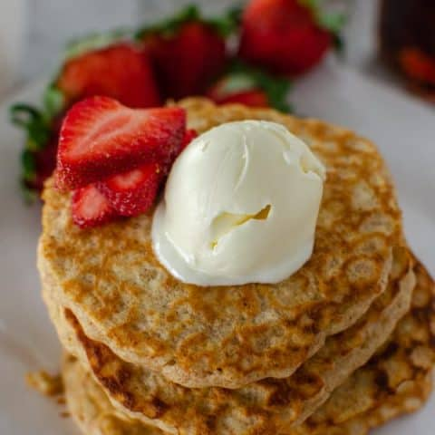 Oatmeal pancake stack with pat of butter and fresh strawberries