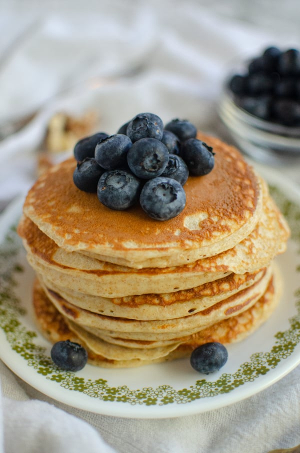 Photo of Greek Yogurt Pancakes on small green floral plate topped with blueberries