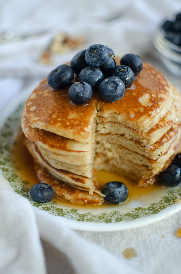 Stack of greek yogurt pancakes with maple syrup and blueberries