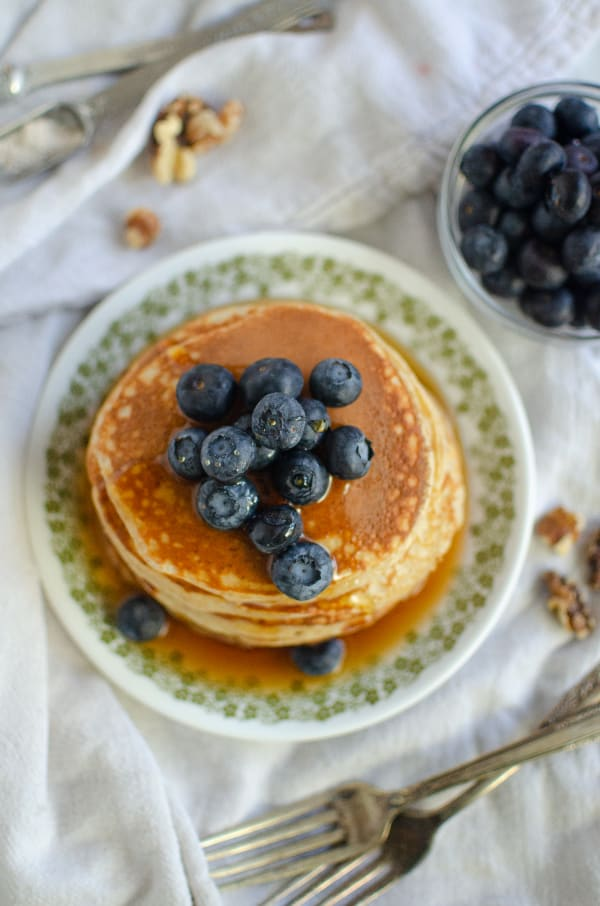 Overhead flatlay of Greek Yogurt pancakes surrounded by forks, walnuts, blueberries