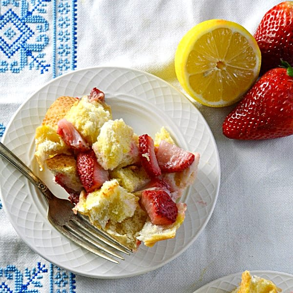 overhead shot of single serving of french toast casserole on small white plate with strawberries and lemons