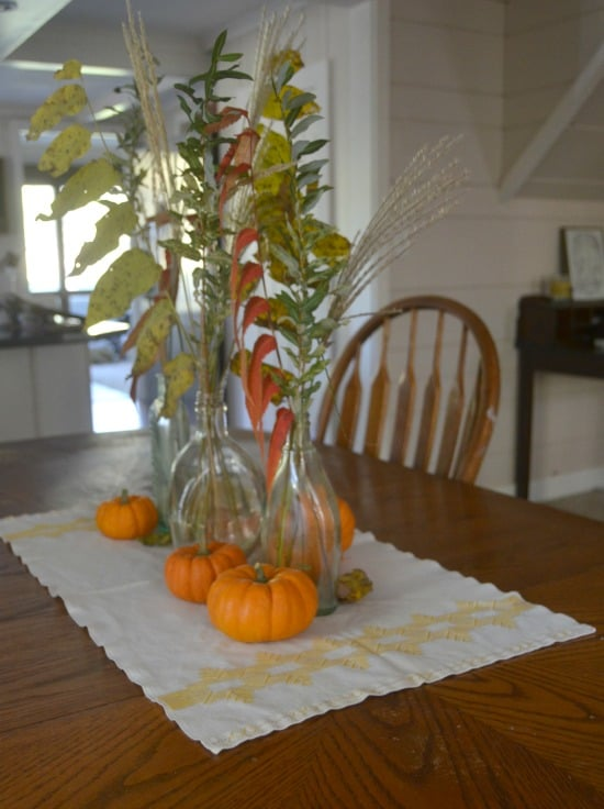 simple thanksgiving table set with mini pumpkins and autumn foliage