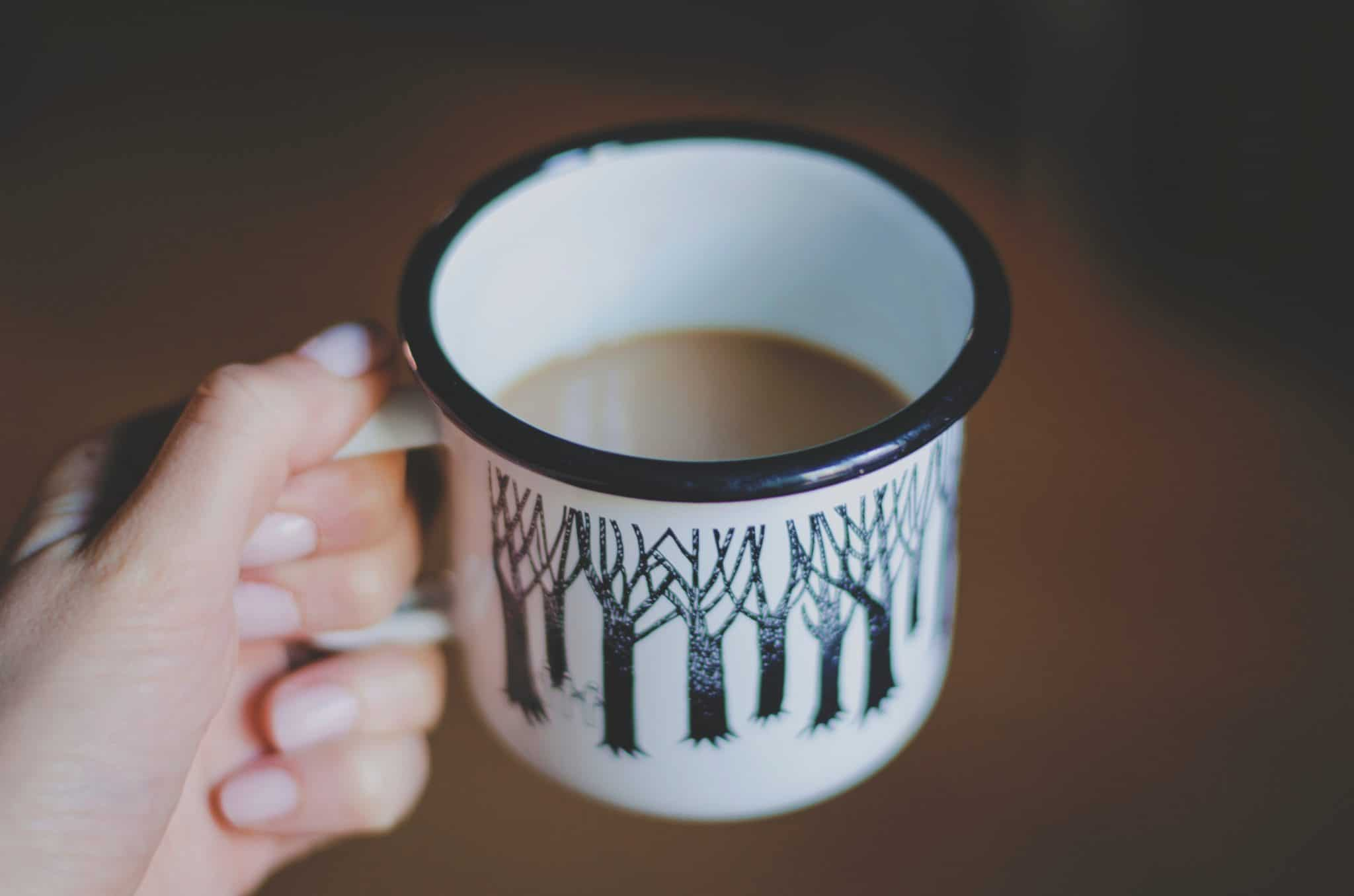 coffee cup with trees in hand with painted nails
