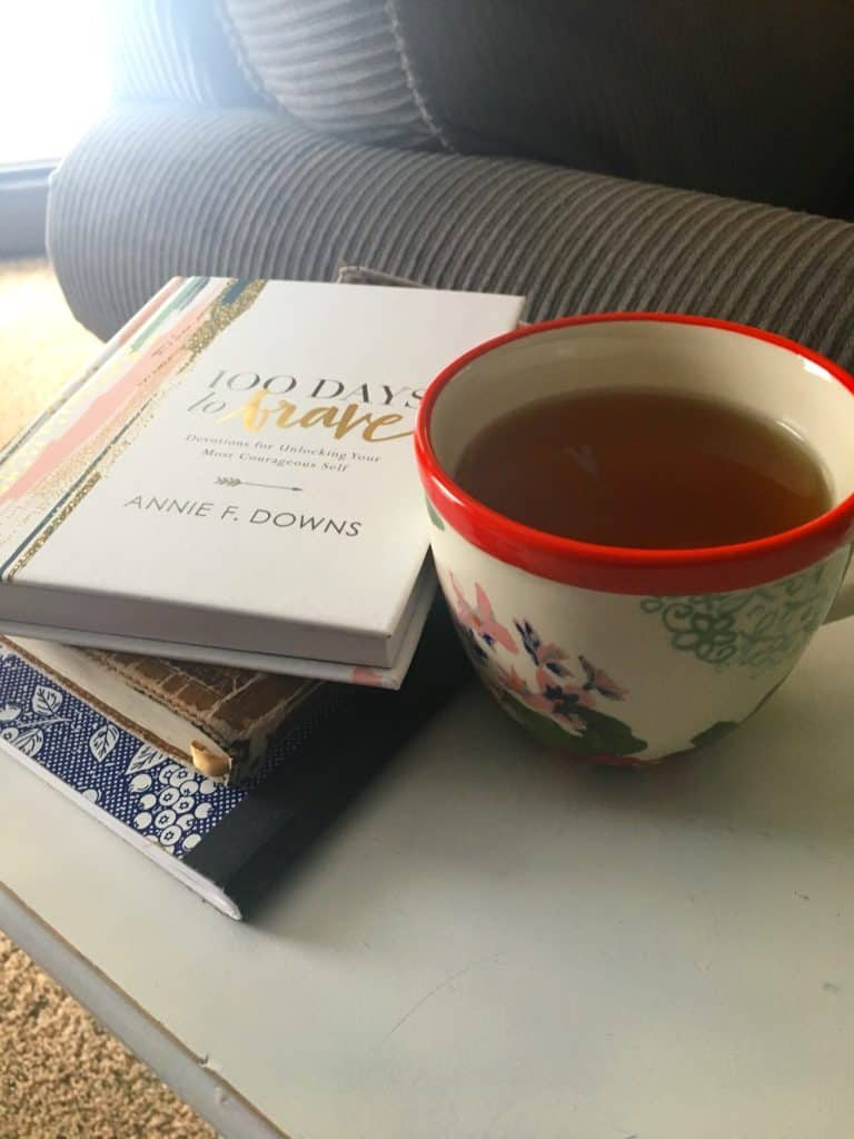 a cup of tea alongside a stack of books