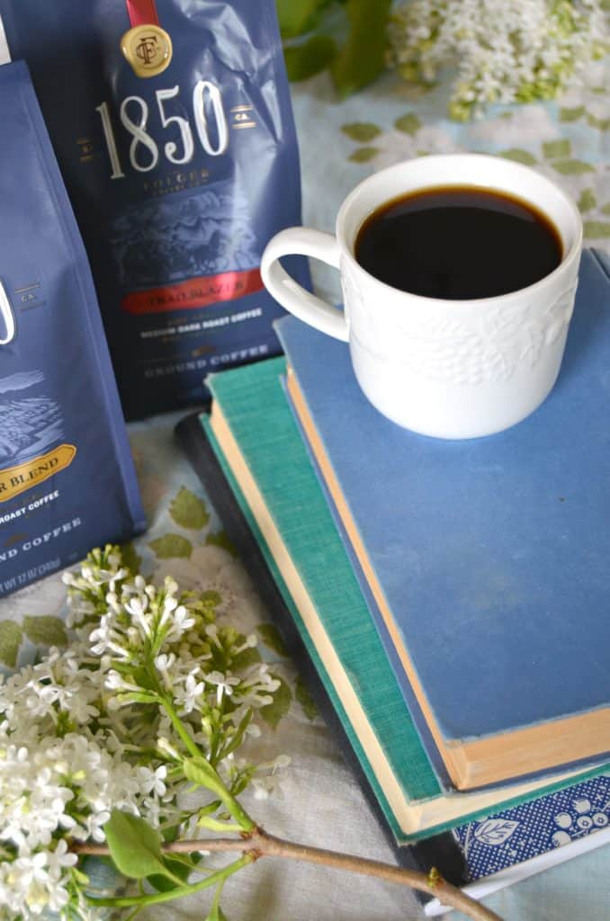 cup of coffee on stack of books with flowers and coffee bags in background