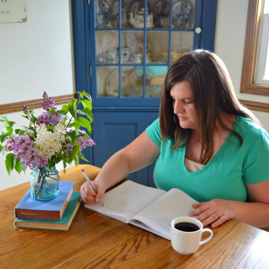 women making list in kitchen with flowers and coffee