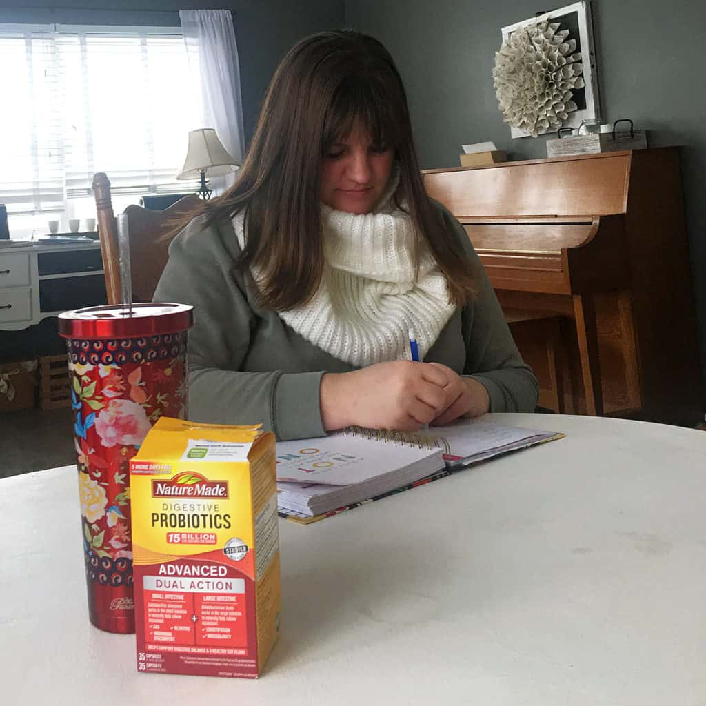 Woman journaling with water and supplement in foreground