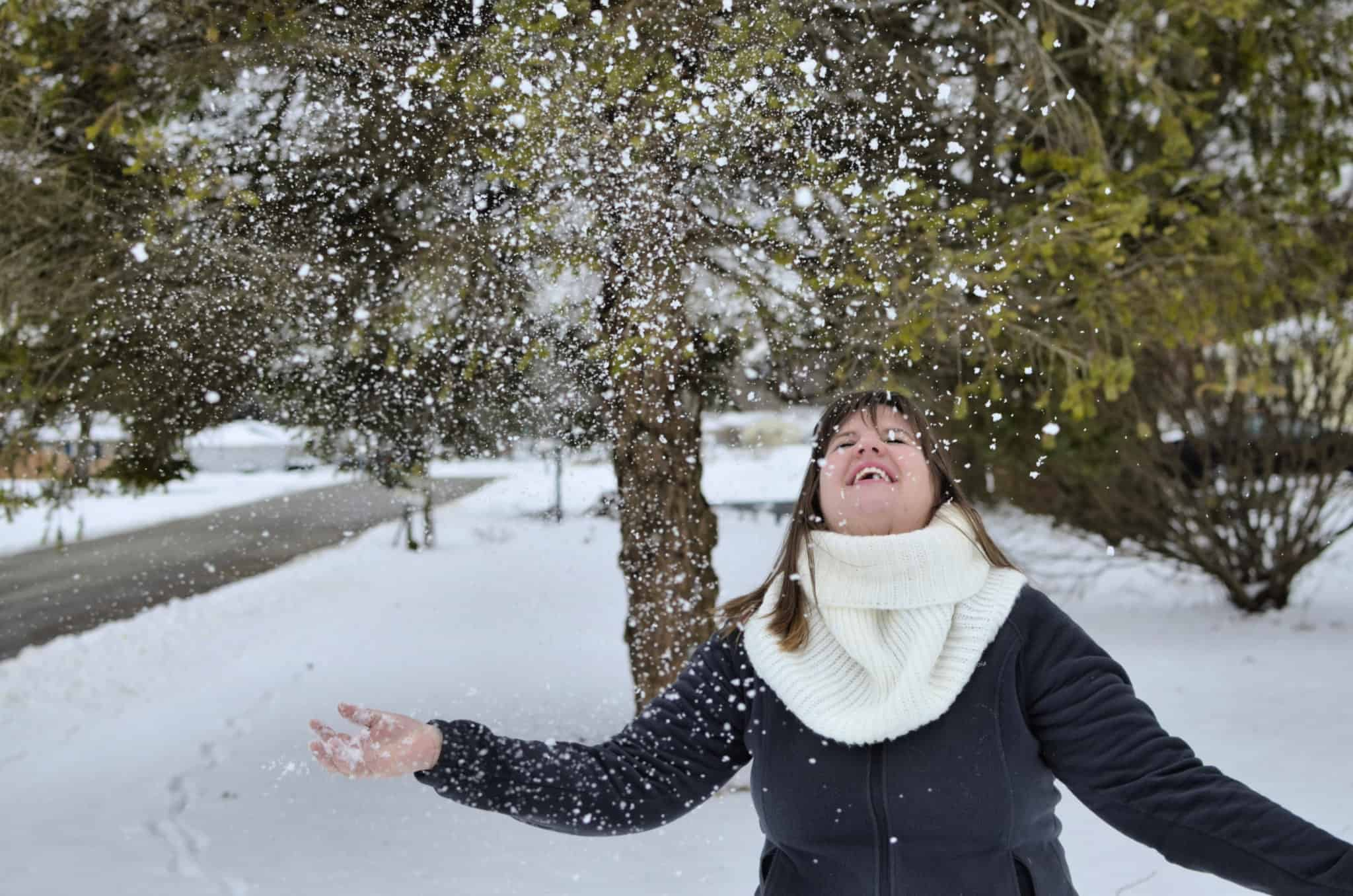 woman laughing and throwing up snow in the winter