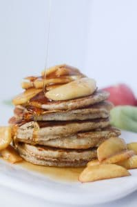 Apple cinnamon pancakes with pour of maple syrup