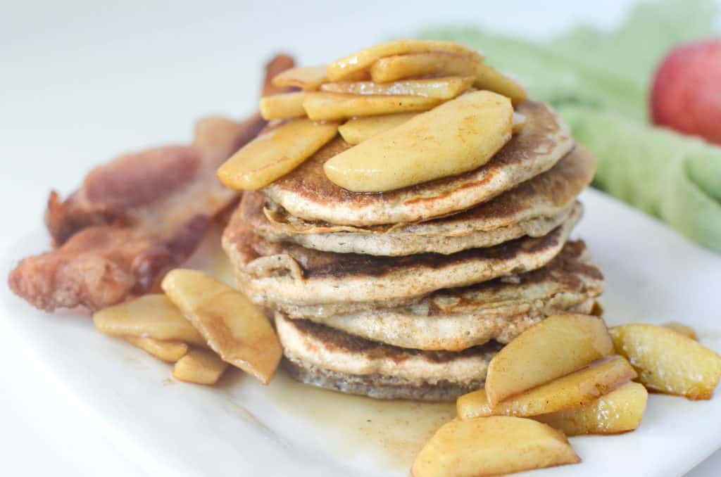 Apple Pancakes topped with cinnamon apples served with bacon