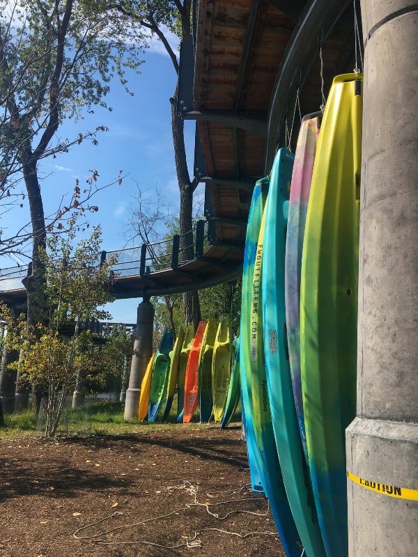 colorful kayaks from fort wayne outfitters lined up under canopy walkway