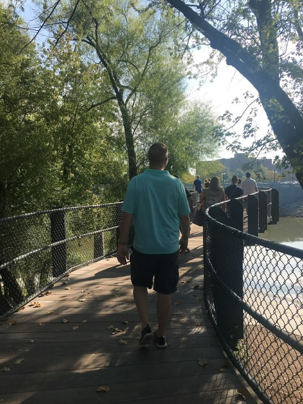 man in teal shirt walking along tree canopy walkway
