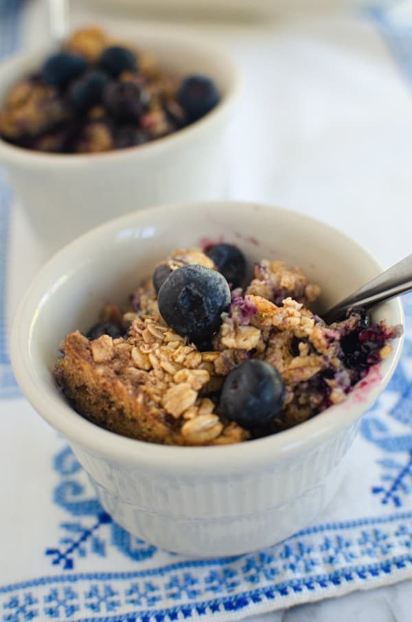 Closeup of two small bowls of blueberry baked oatmeal with spoons