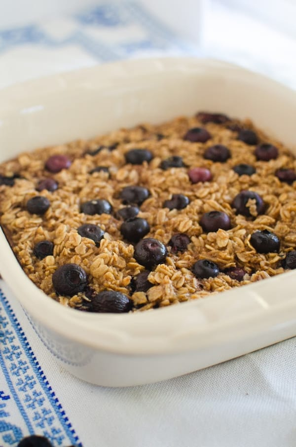Pan of healthy blueberry baked oatmeal on blue and white cloth