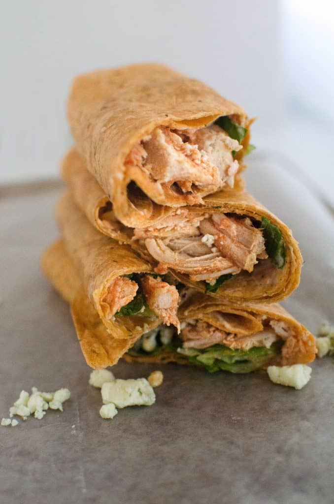 Three buffalo chicken wraps stacked on top of each other on a white wrapper.