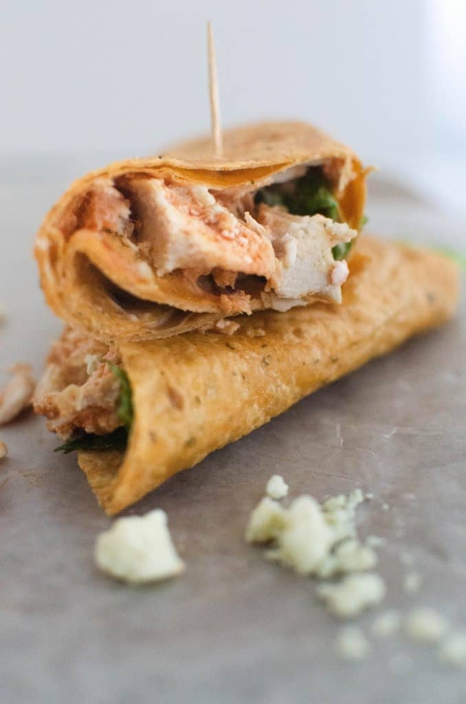 Photo of a wrap with buffalo chicken, romaine and blue cheese with toothpick in the top