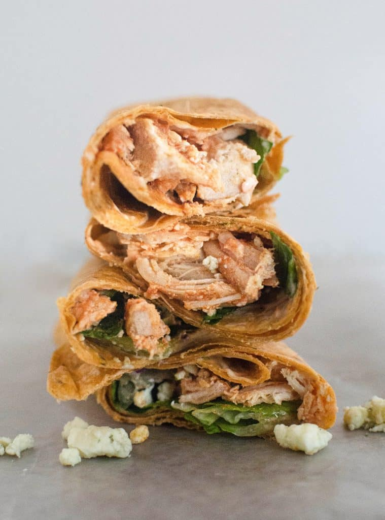 4 buffalo chicken wraps stalked on top of each other with a white background