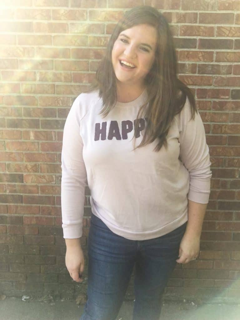 """Woman laughing wearing """"happy"""" sweater"""