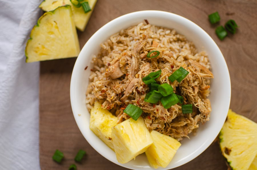 White bowl filled with rice, Hawaiian chicken shredded, green onions and pineapple