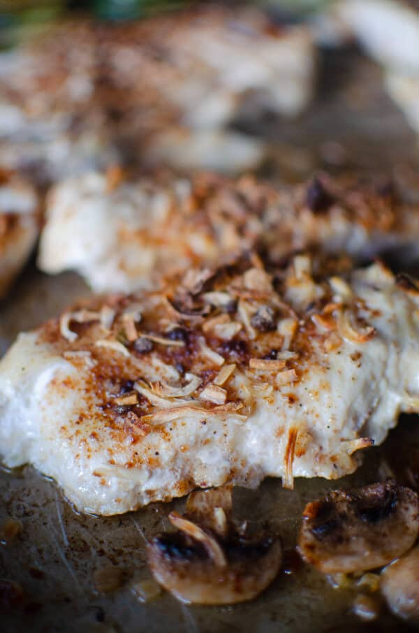 Chicken breast closeup on sheet pan with french onion soup topping