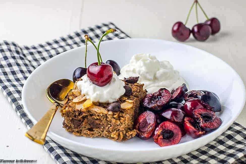 Chocolate espresso baked oatmeal with whip cream and cherries on top