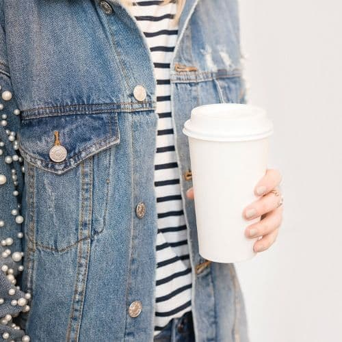 woman in jean jacket with coffee cup
