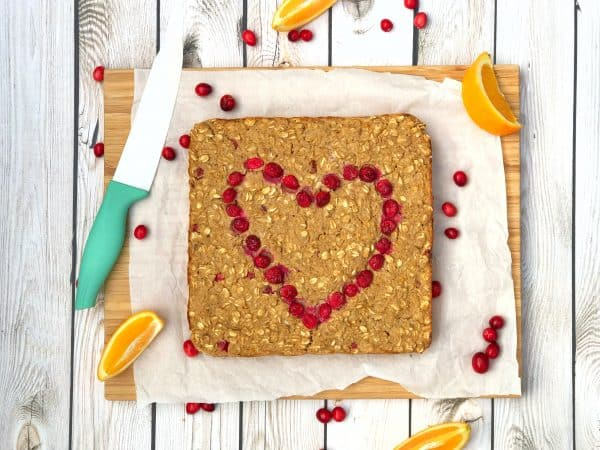 orange cranberry oatmeal baked with heart of cranberries on wooden background with teal knife and cranberries sprinkled around