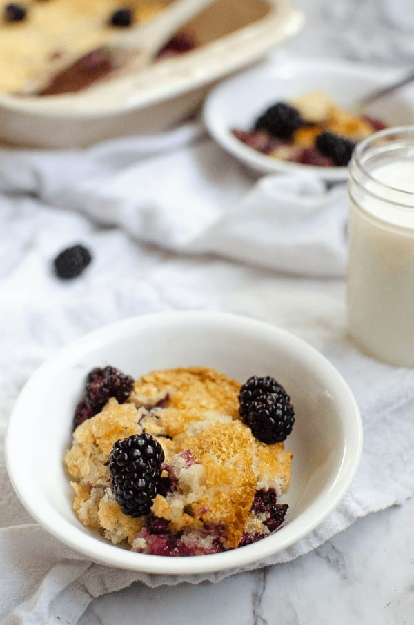 Blackberry cobbler dessert with cup of milk and dish in background