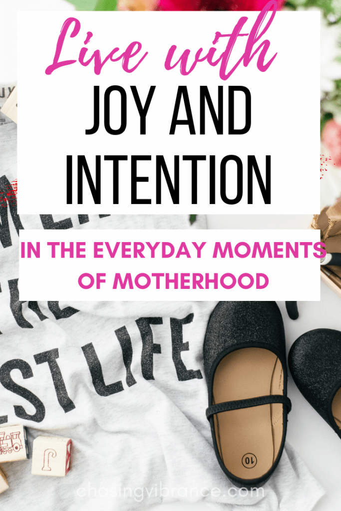 live with joy and intention in the everyday moments of motherhood pin with t-shirt, black toddler shoes, and flowers in the background