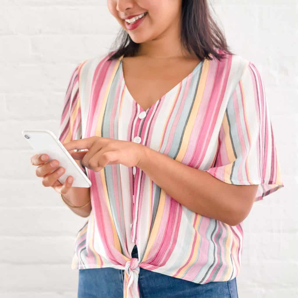 woman in pink top using habit tracker on her phone