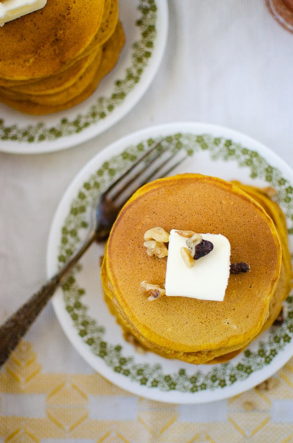 Overhead shot of pumpkin pancakes--large stack with pat of butter and walnuts