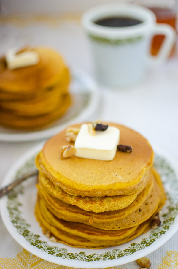 stack of pumpkin pancakes in foreground, second stack and cup of coffee in the background