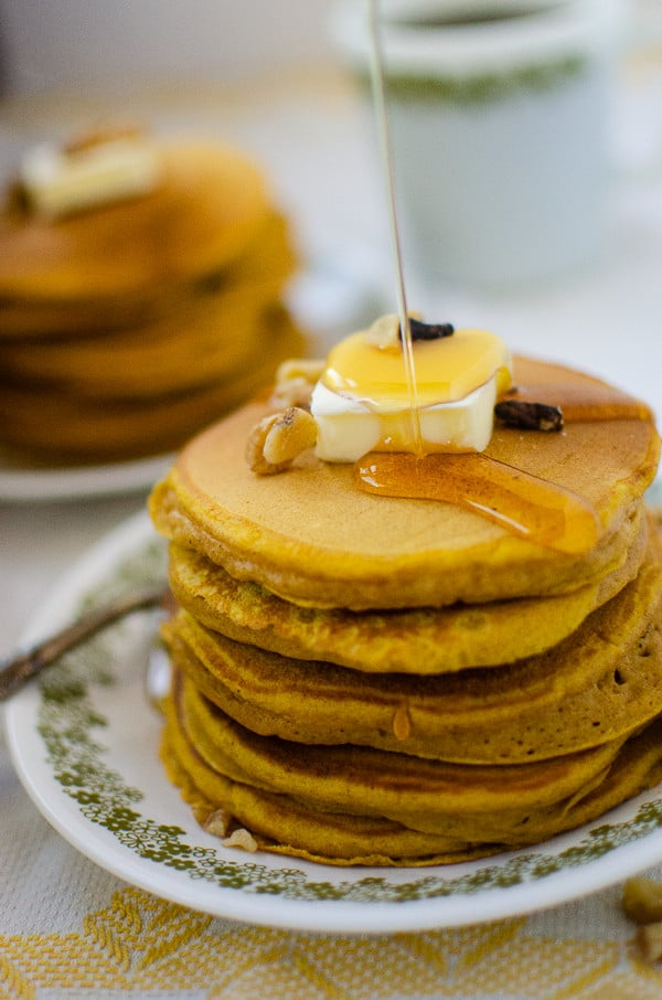 a thick stream of syrup pours down onto a stack of pumpkin pancakes