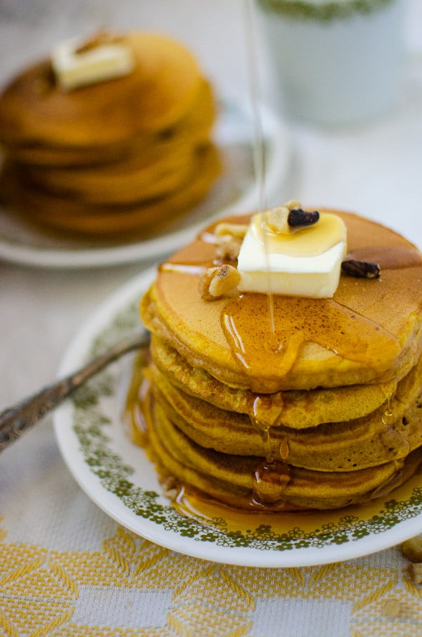 pumpkin pancakes being covered in maple syrup