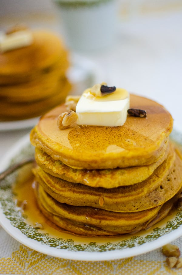 large stack of pumpkin pancakes on plate with golden syrup dripping down
