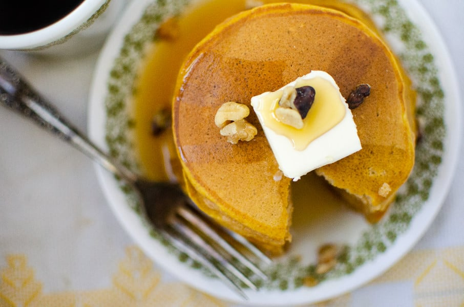 Overhead shot of pancakes with pumpkin, walnuts and butter