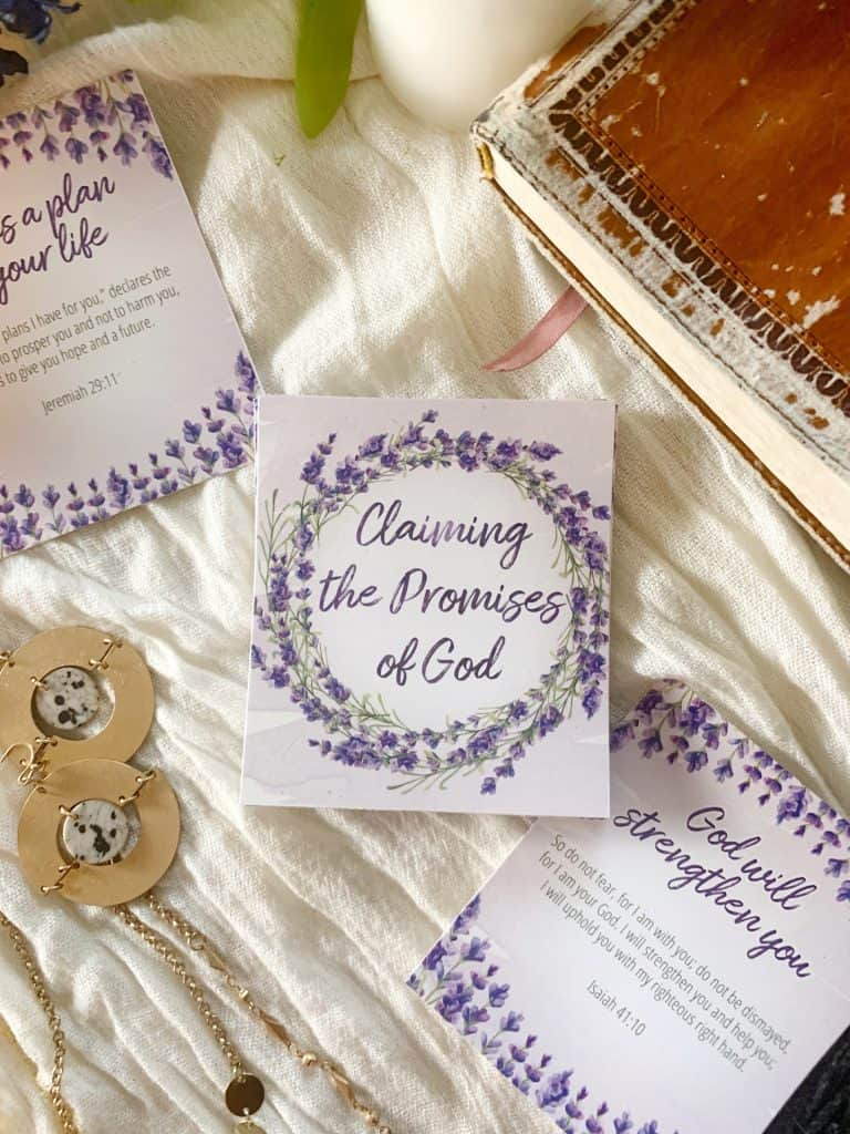 promises of God verse cards on white fabric with earrings, necklace and Bible around it.
