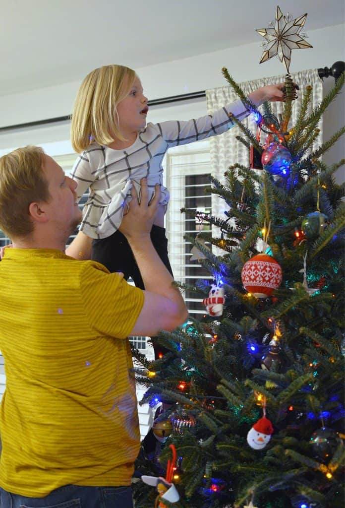 dad lifts girl to put star on christmas tree