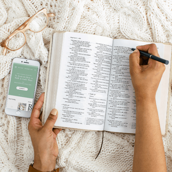 Bible study app on iphone plus person writing in Bible on cozy blanket