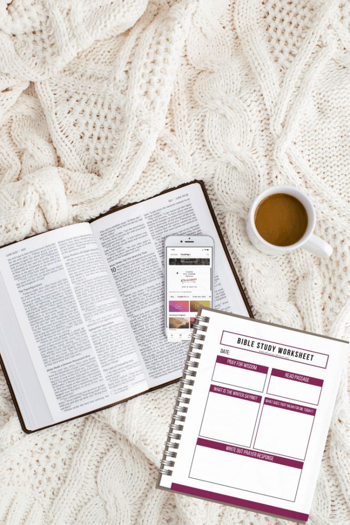 Bible, Bible app on phone, and Bible study worksheet on cozy blanket with cup of coffee