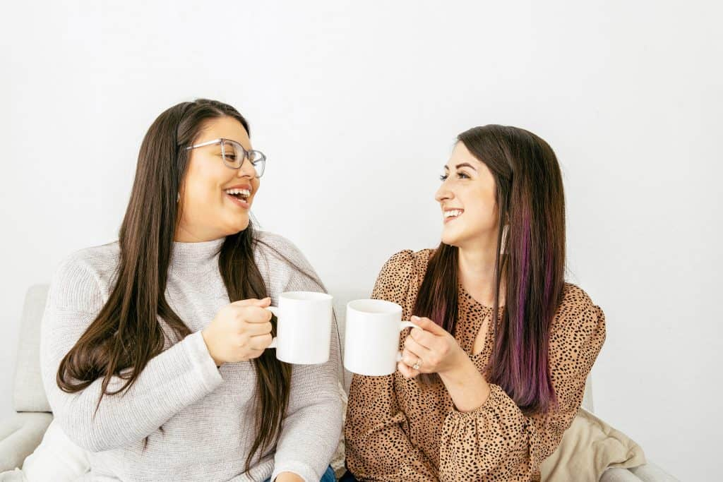 two female friends clinking coffee mugs