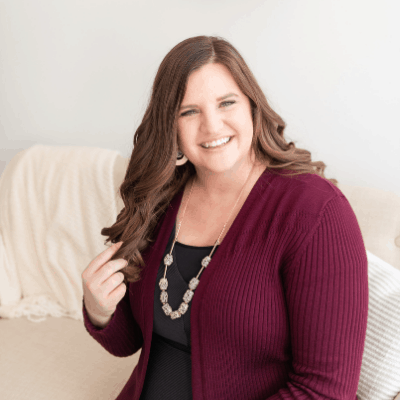 Katie Miller Scott looking at the camera with a big smile and touching her hair. She's wearing a wine colored sweater and a necklace from Target