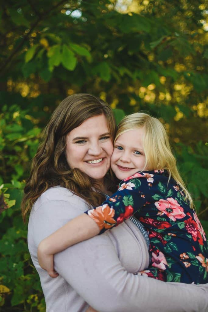 Katie (mom) hugs Layla (daughter) against a woodsy background