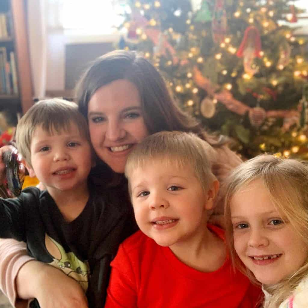 mom and three smiling kids in front of a Christmas tree.